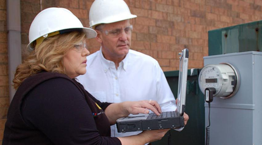 Lisa Queen and Kevin Kemmerer wear hard hats and look at a computer.