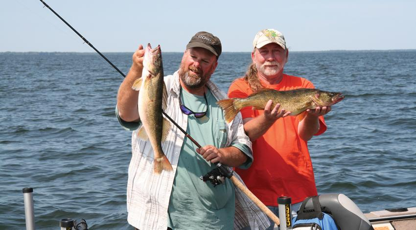 Fishing guide Dave Rose (left) and a client show off part of their catch of Green Bay walleyes during a day on the lake.