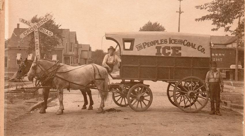 Two men pose with a wagon drawn by horses, designed to carry and deliver ice.