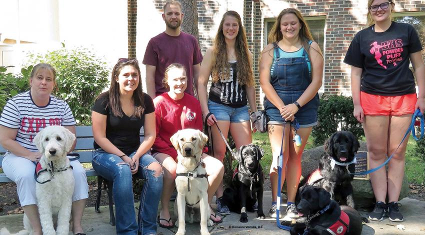 Polar Paws volunteers show off their trainees for the group's founder, Matt Sutton.