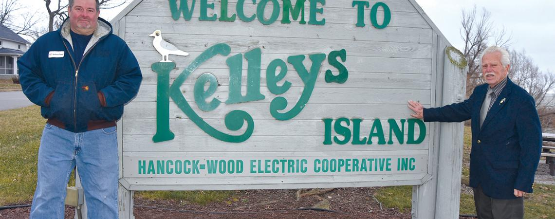 David Ervin and Knute Lahrs pose for a picture beside the sign for Kelleys Island.